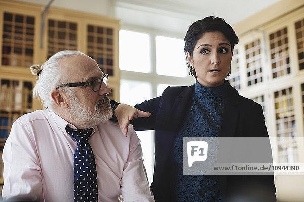 Zuverlässige Anwältin im Gespräch mit Senior-Mitarbeiterin in der Bibliothek