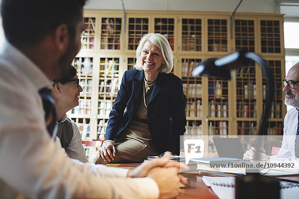 Happy senior lawyer sitting on table during meeting in library