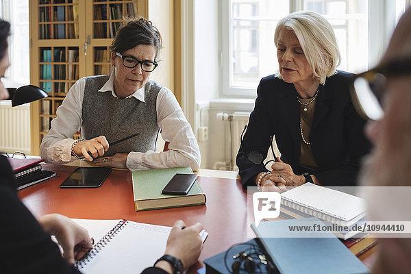 Profis diskutieren während der Sitzung am Tisch in der Rechtsbibliothek