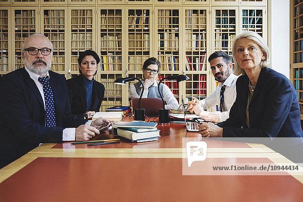 Porträt der Anwälte im Vorstandszimmer gegen das Bücherregal