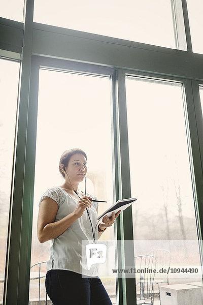 Nachdenkliche Geschäftsfrau mit Notizblock und Stift im Büro