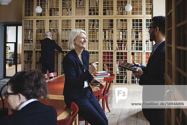 Glücklicher Senior-Anwalt im Gespräch mit Kollegen im Vorstandszimmer der Bibliothek