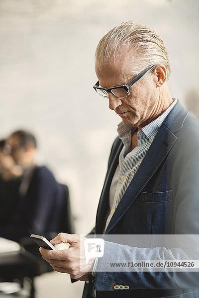 Senior Geschäftsmann mit Handy im Büro