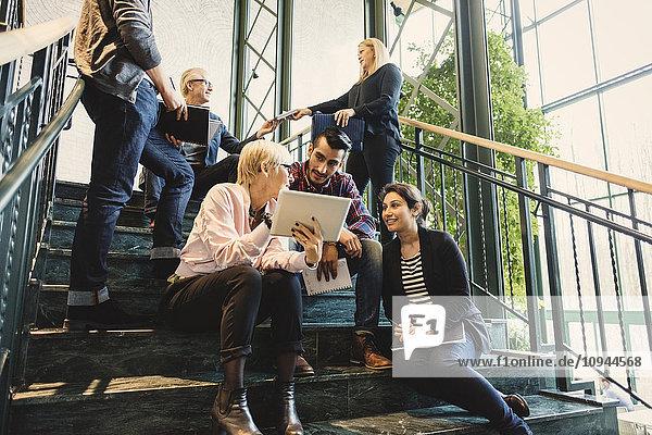 Multiethnische Geschäftsleute diskutieren auf der Treppe im Kreativbüro