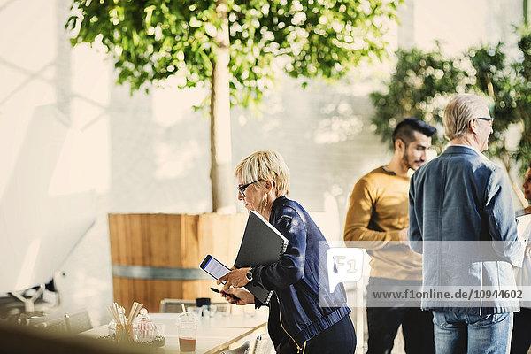 Reife Geschäftsfrau mit Kartei und Handy steht den Kollegen im Kreativbüro zur Seite