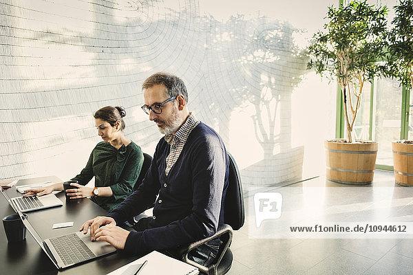 Multiethnische Geschäftsleute mit Laptops am Tisch im Kreativbüro