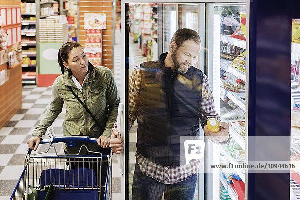 Paare kaufen Lebensmittel  während sie im Supermarkt am Kühlschrank stehen.