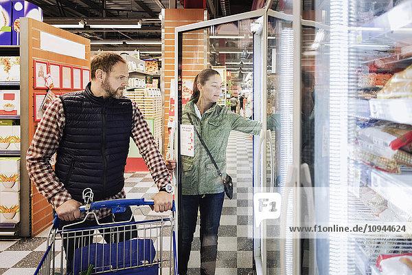 Paare  die Lebensmittel kaufen  während sie im Kühlregal stehen.