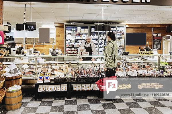 Verkäuferin als Assistentin der Frau im Supermarkt
