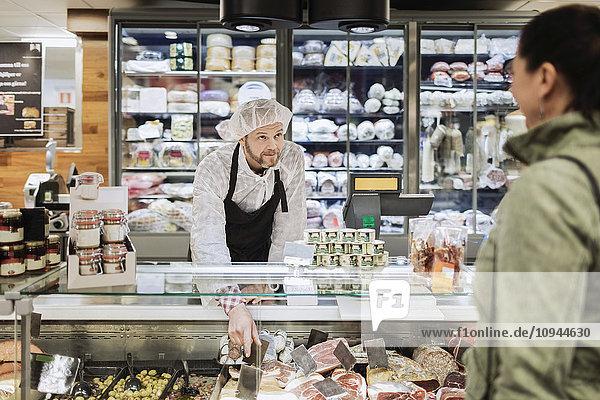 Verkäuferin mit Blick auf die Kundin während sie im Supermarkt assistiert.