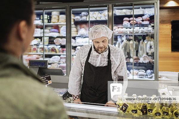 Verkäuferin mit Kundin im Supermarkt