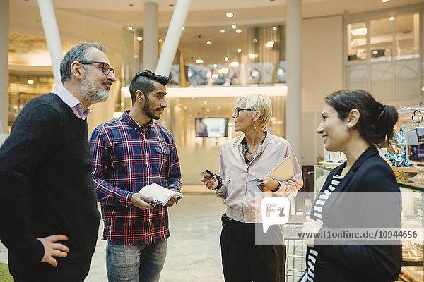 Reife Geschäftsfrau mit Kreditkarten im Gespräch mit Kollegen im Büro