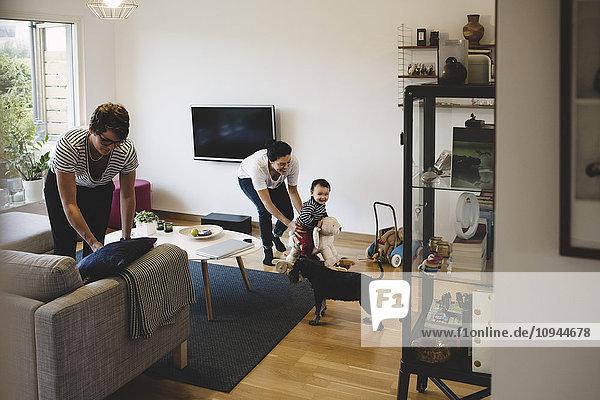 Mutter und kleines Mädchen spielen  während Frauen zu Hause arbeiten