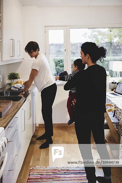 Mutter trägt ein kleines Mädchen  während die Frau an der Küchentheke arbeitet.