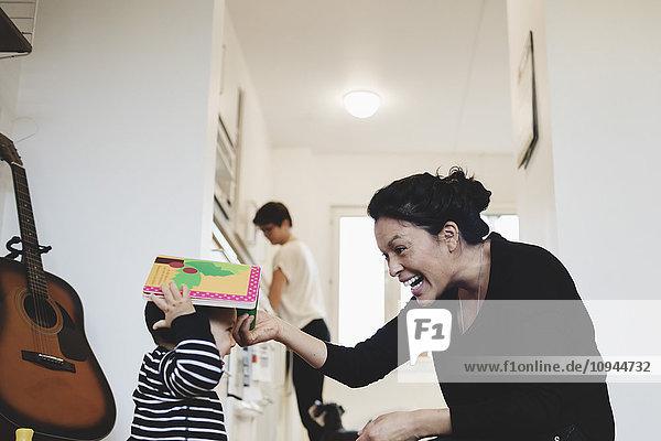 Mutter spielt mit dem Mädchen  während die Frau im Hintergrund steht.