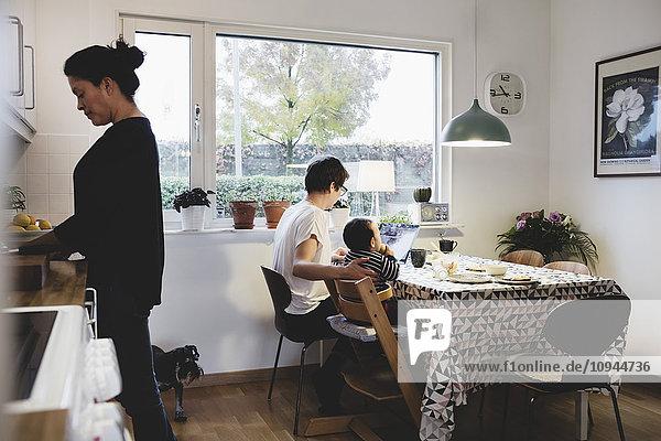 Frau arbeitet und Mutter sitzt mit Mädchen in der Küche