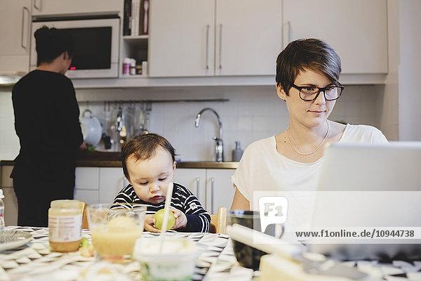 Mutter mit Laptop neben Baby Girl während der Arbeit in der Küche