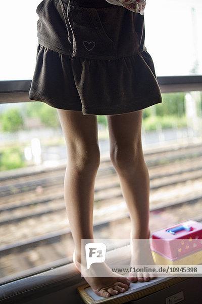 Girl (4-5) on tiptoe on shelf in train  low section