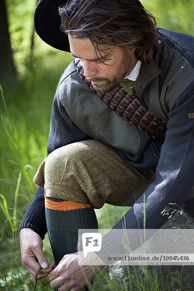 Man wearing hunting clothing tiding up shoelace