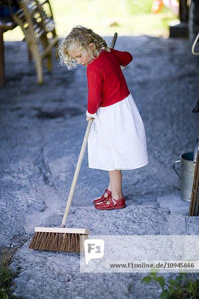 Girl sweeping garden path