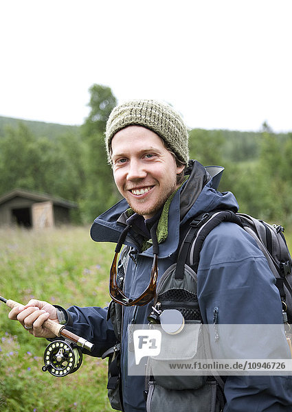 Portrait of smiling mid adult man with fishing rod