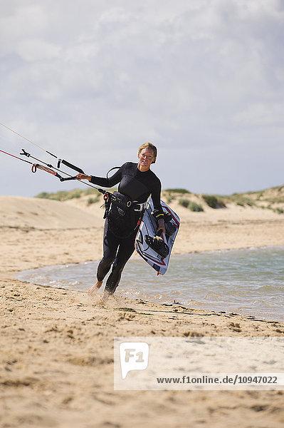 Paraglider walking on beach