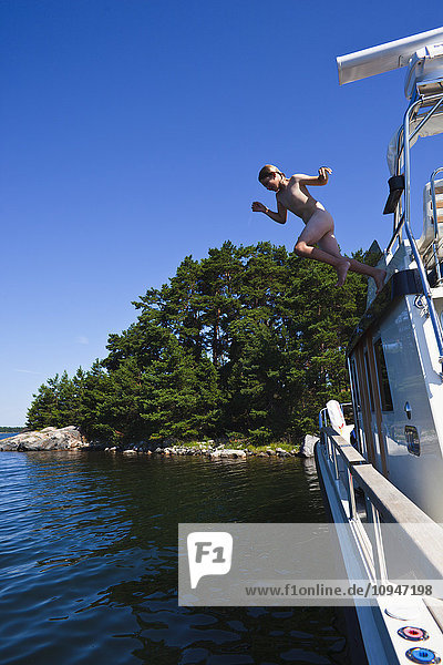 Boy jumping from boat