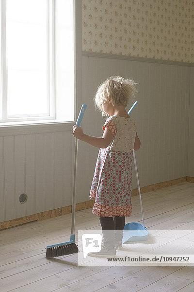 Girl sweeping floor