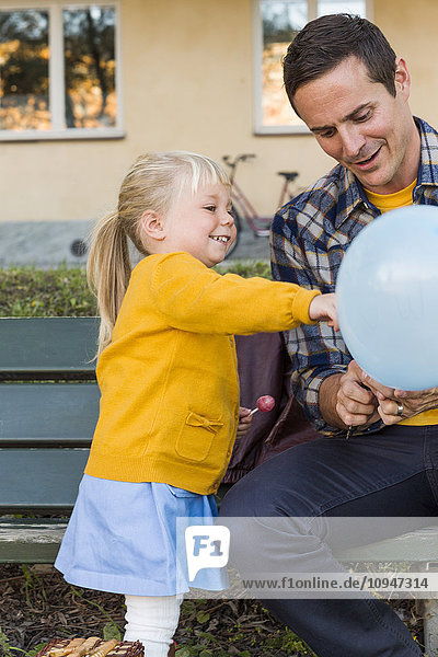 Father with daughter holding balloons