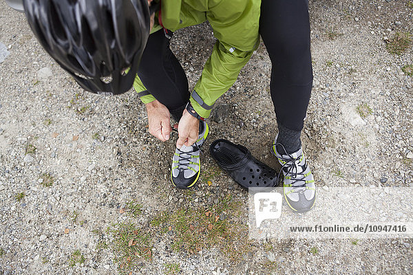 Mature man putting on cycling shoes