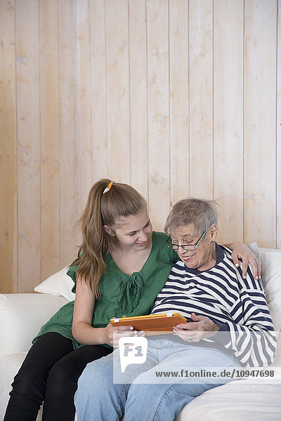 Grandmother and granddaughter using tablet