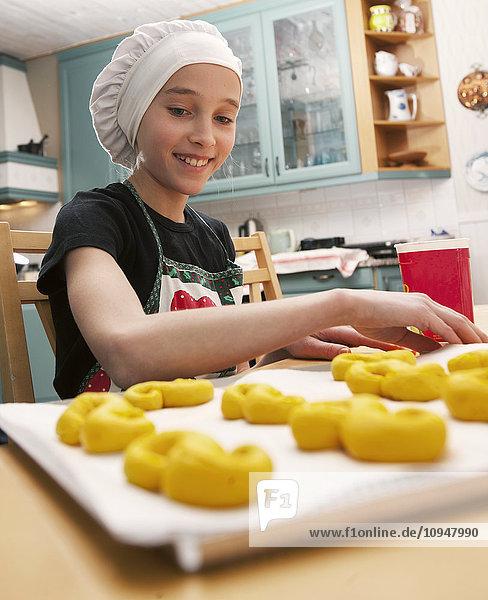 Smiling girl making traditional Swedish saffron rolls