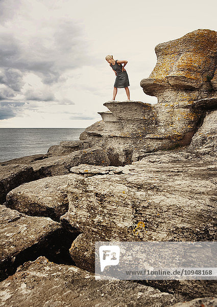 Woman standing on rock on coast