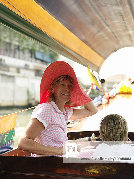 Smiling woman with son on boat