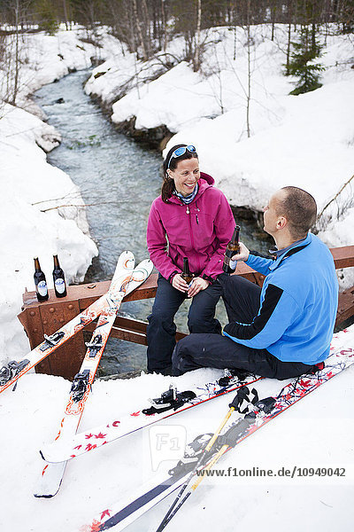 Couple relaxing with beers at stream