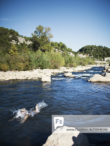 Woman swimming in small river
