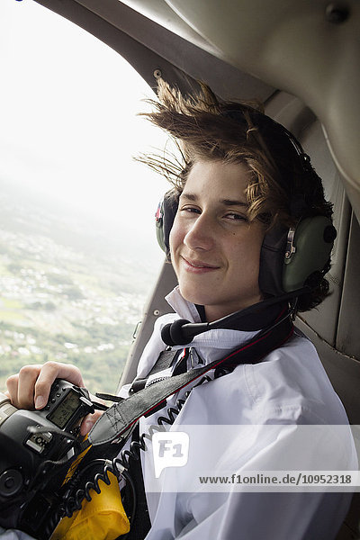 Teenage boy in helicopter holding camera