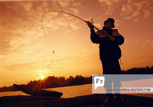 Man with spinning rod fishing in the sunset.