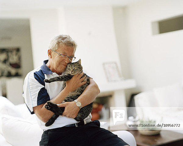 A man holding a cat in his arms  Sweden.
