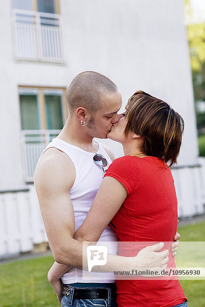 Man and woman kissing outside a dwelling-house  Sweden.