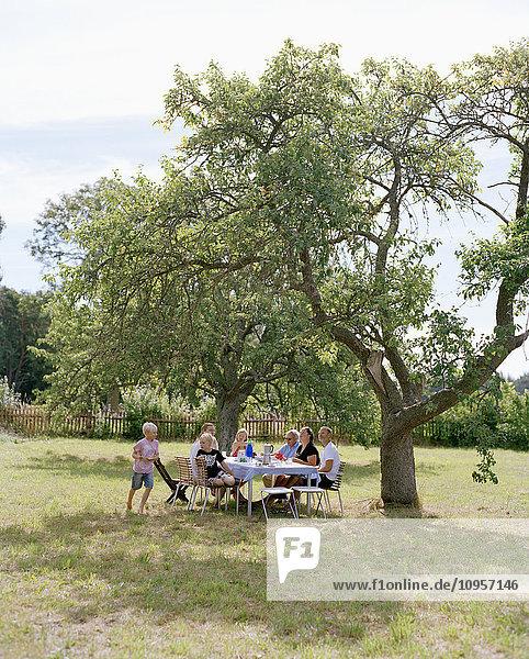 Multi-generation family having dinner in the garden  Sweden.