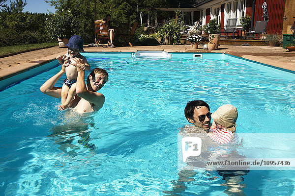 Two dads with one small children in a swimming pool  Sweden.
