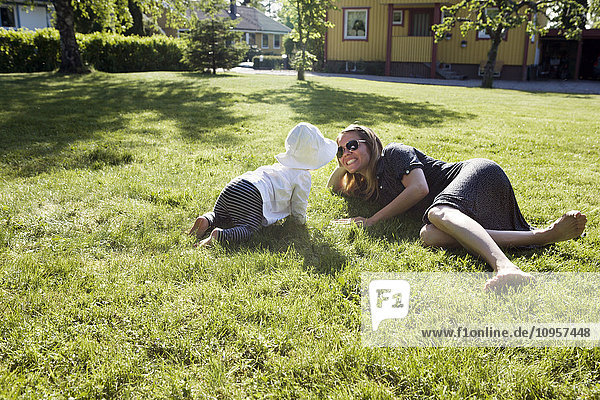Woman and small child playing in the grass  Sweden.