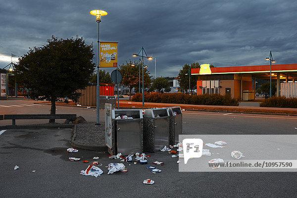 Overfull litterbins on a desert parking lot  Sweden.
