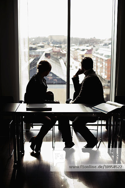 Two people in an office looking out of a window,  Sweden.