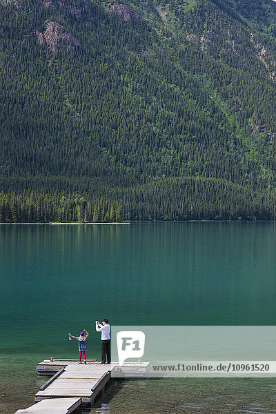 Mother and daughter on a dock at Muncho Lake Provincial Park  British Columbia  Canada  Summer