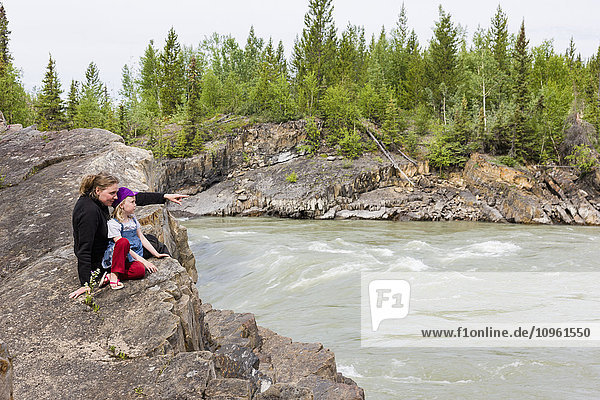 Mother and daughter sit on a rock riverbank and view Liard River  Whirlpool Canyon  British Columbia  Canada  Summer