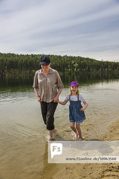 Mother and daughter wade with bare feet in Lucky Lake  Yukon Territory  Canada  Summer