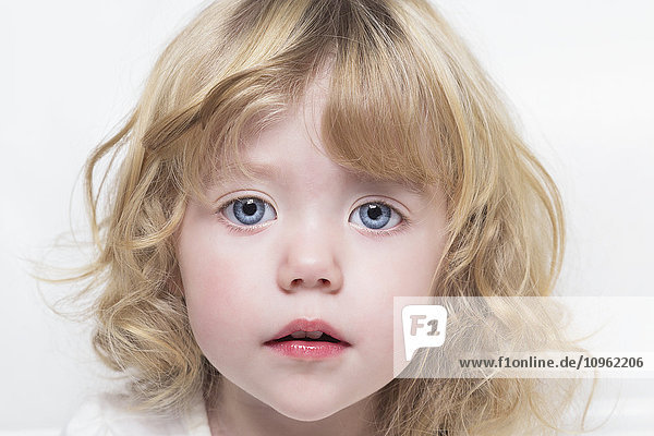 'Close up of a toddler with beautiful big blue eyes and blond curly hair; Spruce Grove  Alberta  Canada'