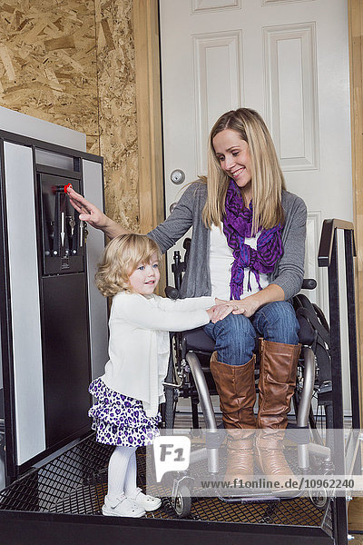 'Young disabled mother with her daughter using wheelchair powered device to assist with mobility; Spruce Grove  Alberta  Canada'